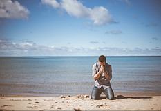 What's happiness in life - man kneeling on sandy beach