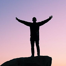 What is a Winning Attitude - arms stretched out on top of a rock